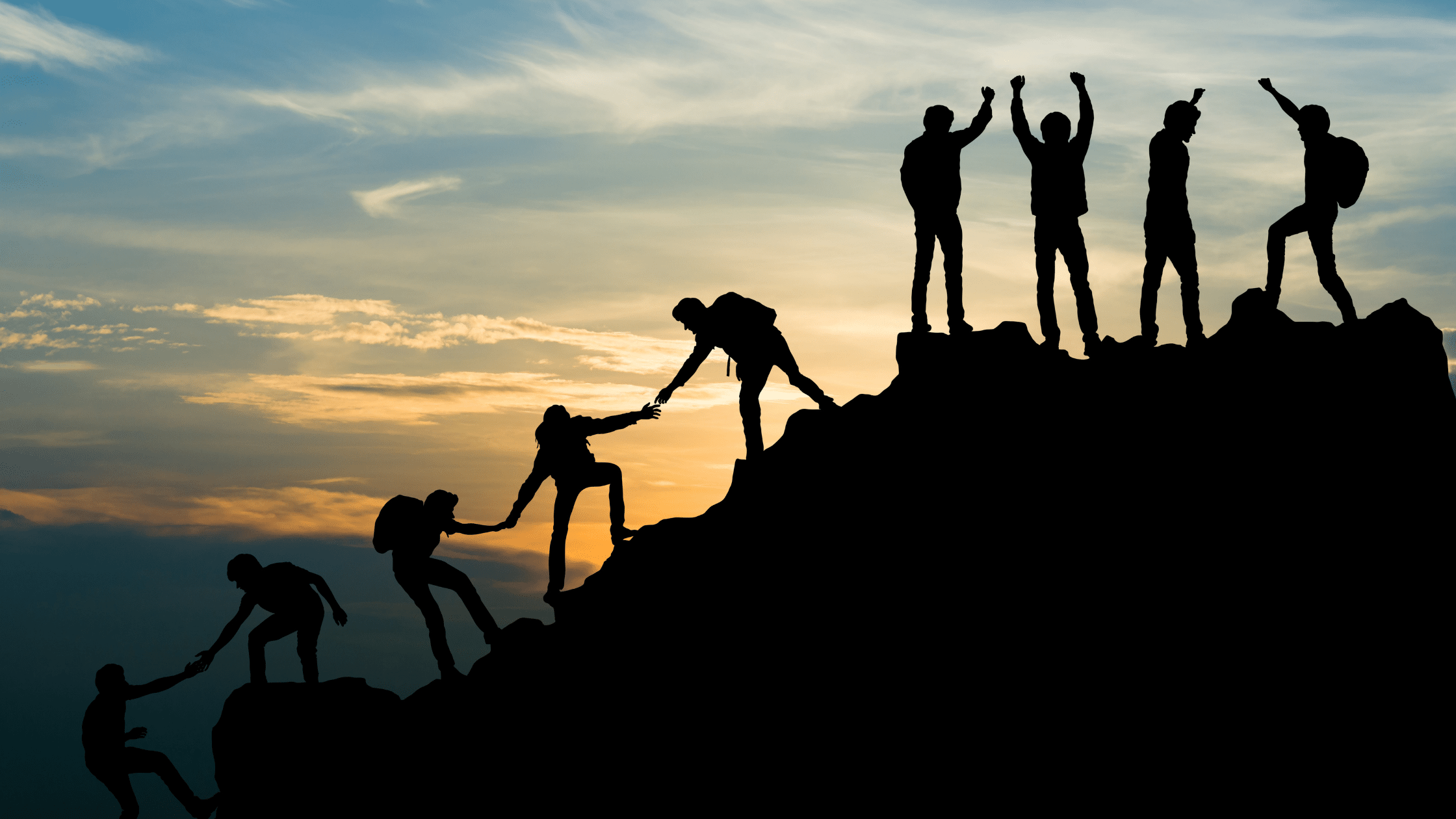 photo of people helping each other up a mountain at sunrise
